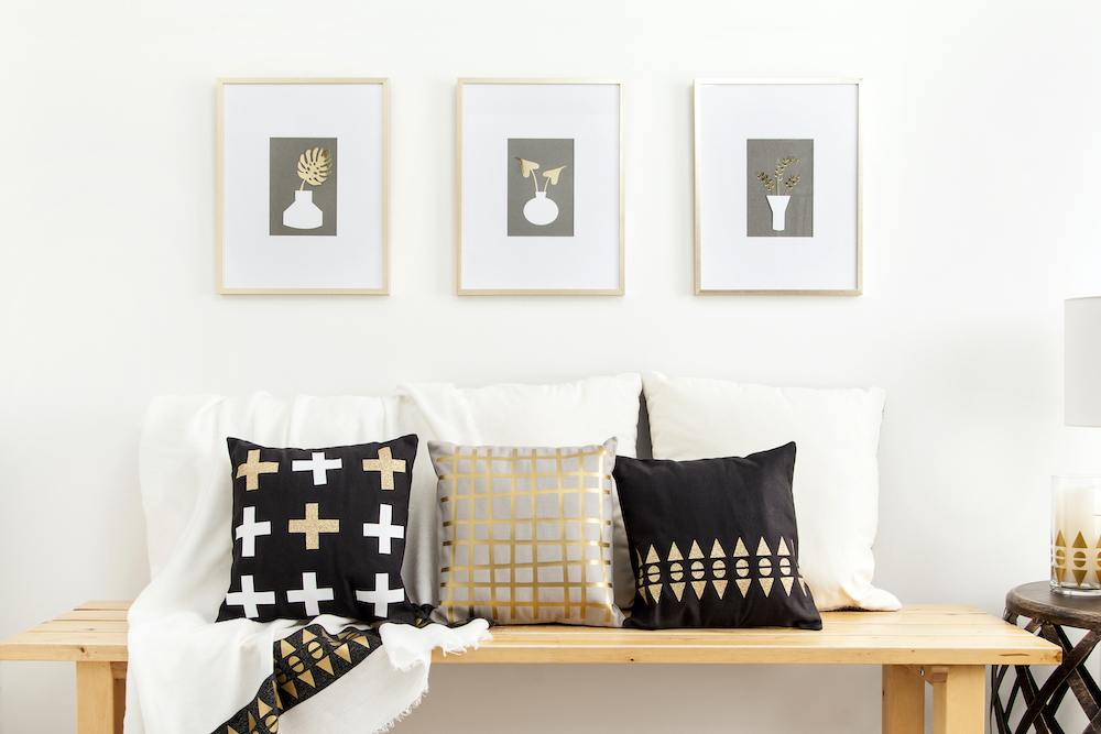 A bench is decorated in metallic decor, including decorative pillows and golden wall art prints