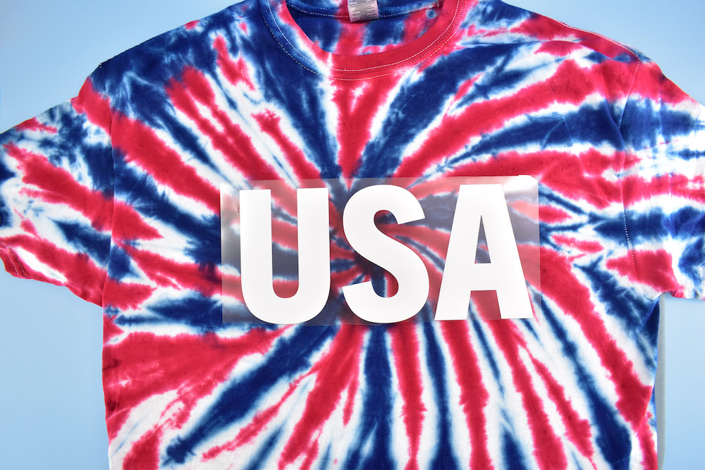 """A white """"USA"""" logo is laid flat on a red white and blue tie-dyed shirt"""
