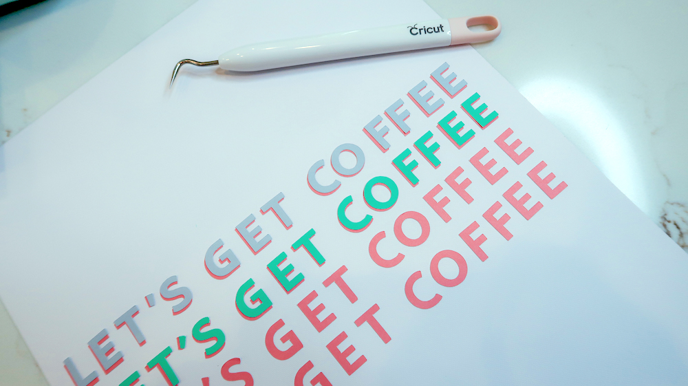 """A colorful print for dorm room decor spells the phrase """"let's get coffee"""" on white cardstock"""