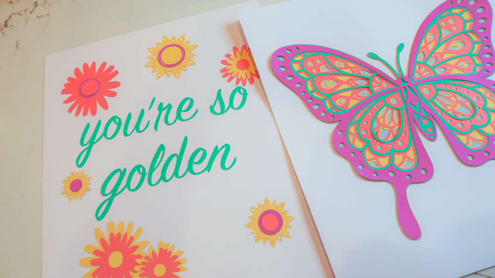 """A pastel butterfly print sits near a print that reads """"you're so golden"""""""