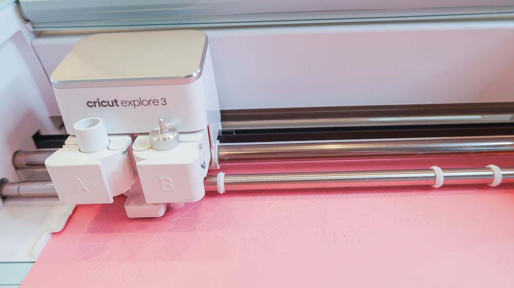 A close up of the Cricut Explore 3 machine making a pink print for dorm room decor