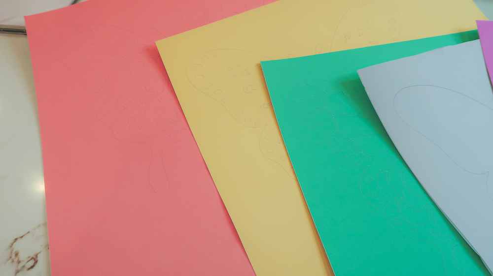 4 sheets of pink, yellow, green, and blue pastel cardstock sit on a granite countertop