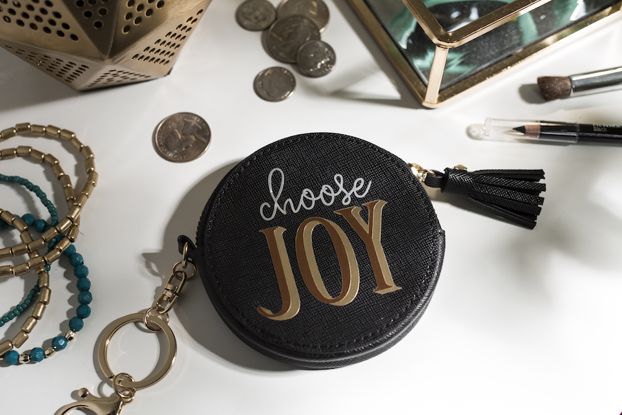 """A black leather coin purse with the phrase """"choose joy"""" sits on a white tabletop"""