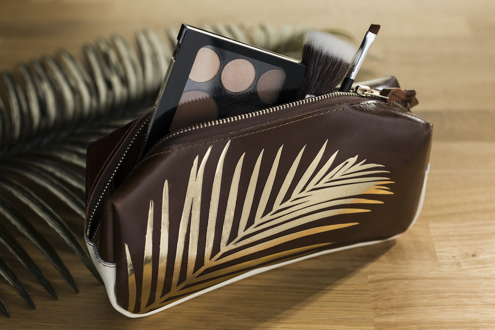 A brown cosmetic pouch with a gold foil palm leaf design holds an array of makeup and makeup tools