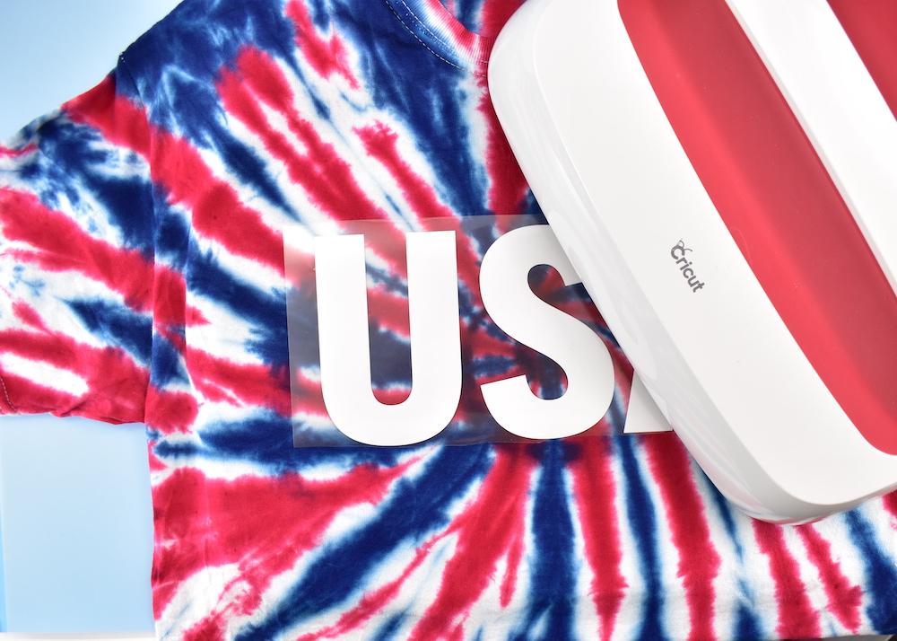 "A white ""USA"" logo is ironed onto a shirt using a Cricut EasyPress"