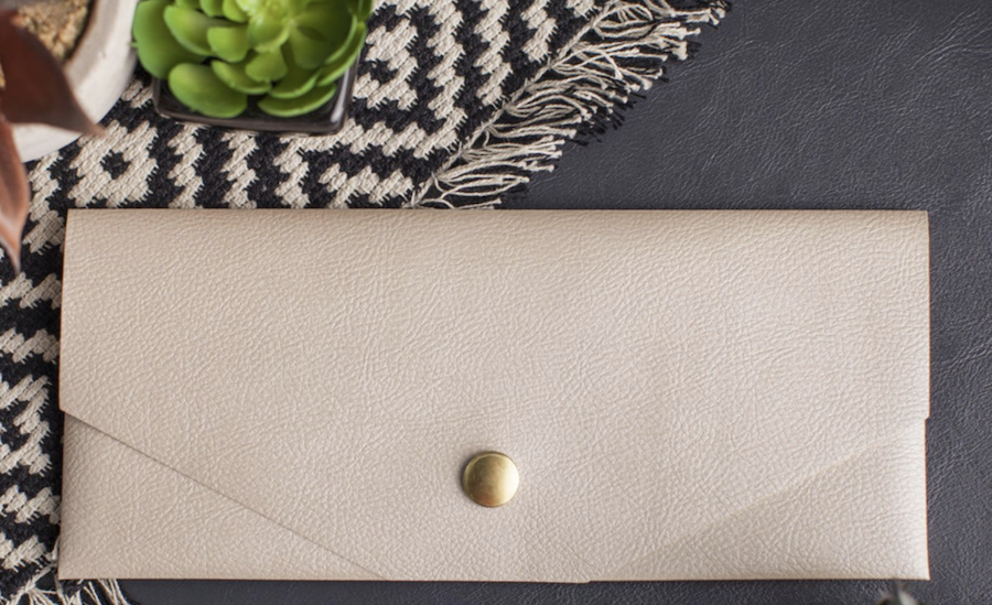 A neutral colored, faux leather clutch handbag sits on a leather countertop