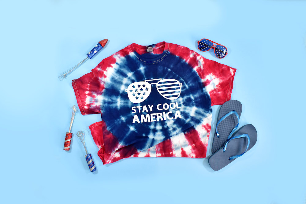 A red, white, and blue tie-dye tee with a white, patriotic Cricut decal on a blue background