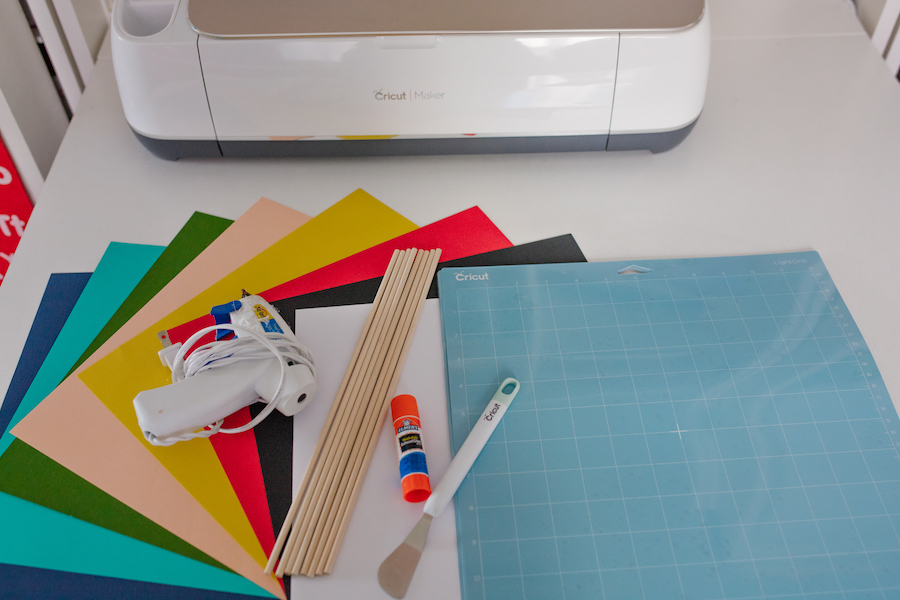 An array of Cricut supplies prepped to create back-to-school photoshoot props sits on a white countertop