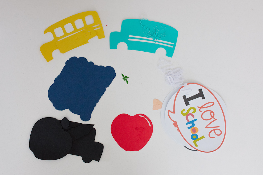 Cut paper elements for back-to-school photoshoot props sit on a white table