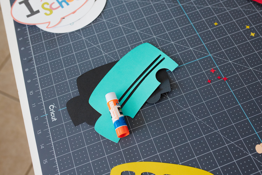 Glue is used to adhere different layers of cut cardstock to one another to create back-to-school photoshoot props