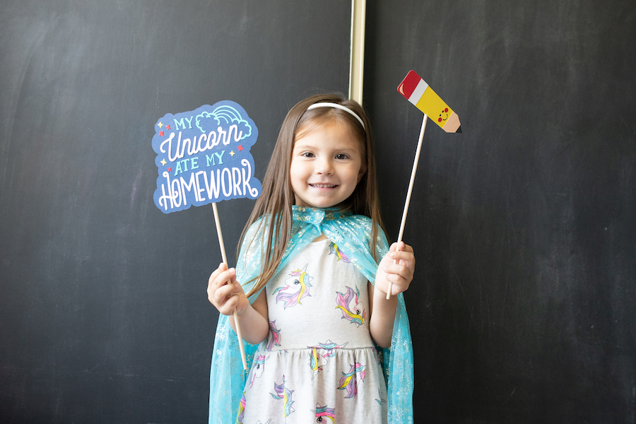 A little girl holds up back-to-school photoshoot props