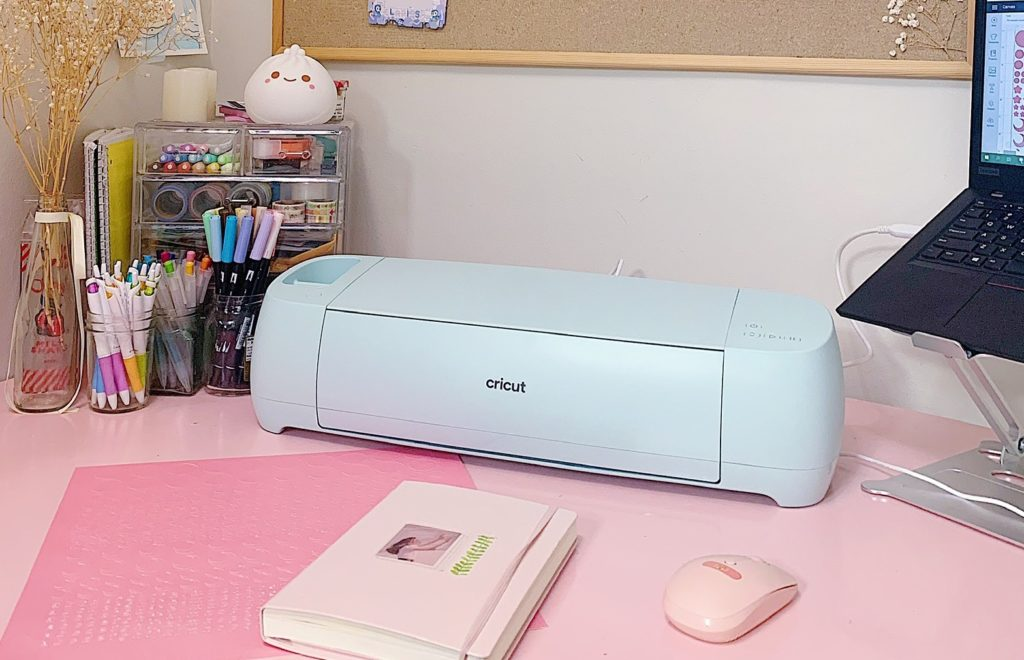 A Cricut Explore 3 machine sits on a pink desk, awaiting cut instructions to create bullet journaling stickers