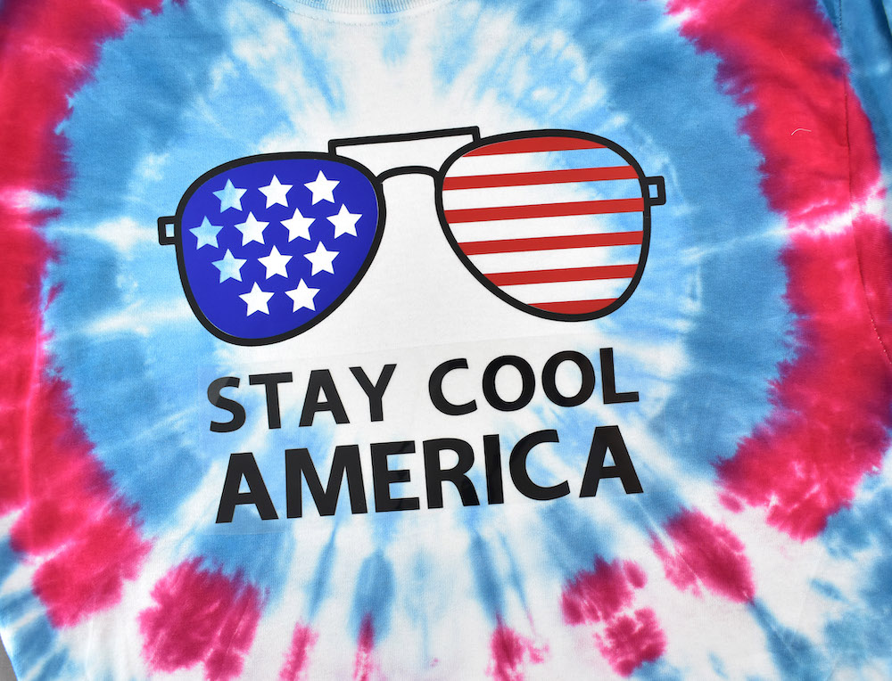 """A red, white, and blue tie-dye shirt is embellished with a """"stay cool America"""" design with aviator glasses"""