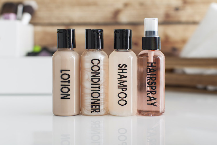 Small travel bottles with black vinyl labels on them, describing the cosmetics they hold
