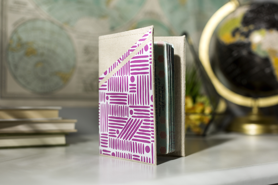 A beige passport holder is covered with a pink patterned design