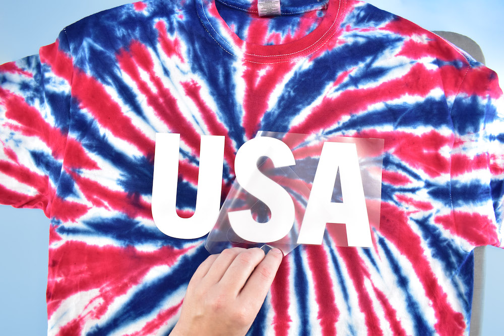 """Plastic is peeled from a vinyl """"USA"""" design applied to a red, white, and blue tie dyed tee"""