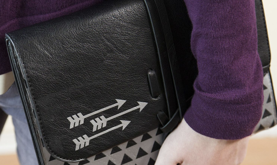 Someone holds a black and grey leather teach sleeve