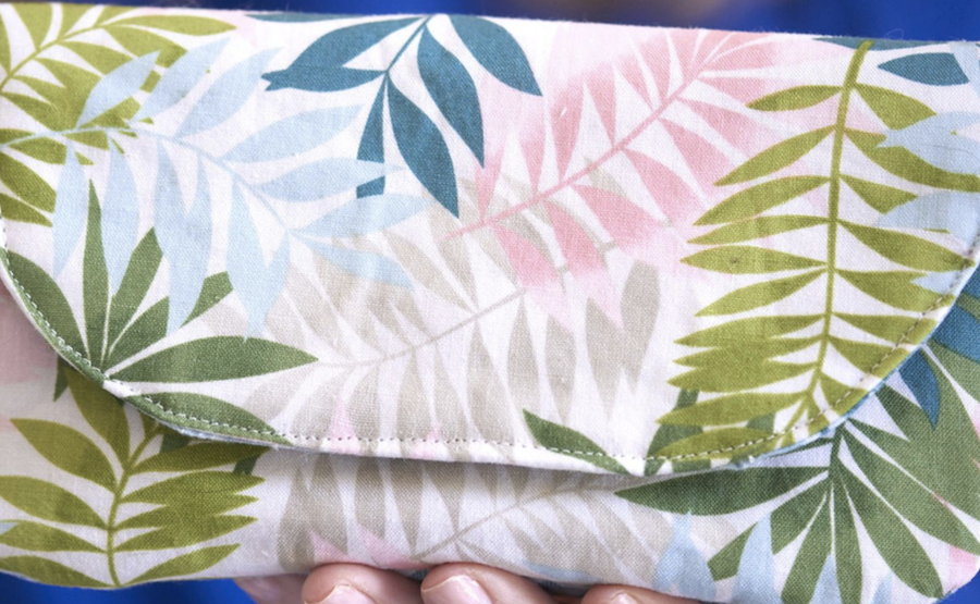 A tropical, leaf pattered wristlet rests in someone's hands