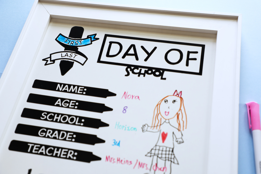 A back-to-school photo shoot whiteboard sits on a blue background