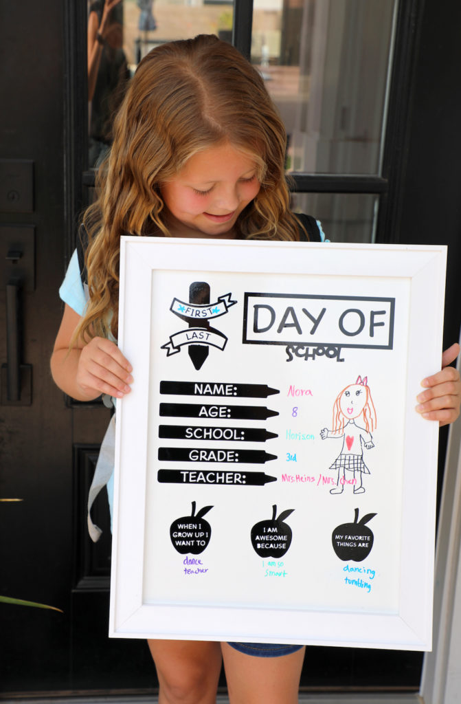 A little girl holds up her drawings and answers written on a back-to-school white board photo shoot prop
