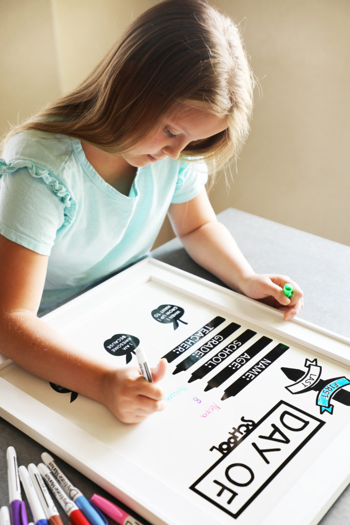 A young girl decorates a back-to-school photo shoot white board prop with dry erase markers
