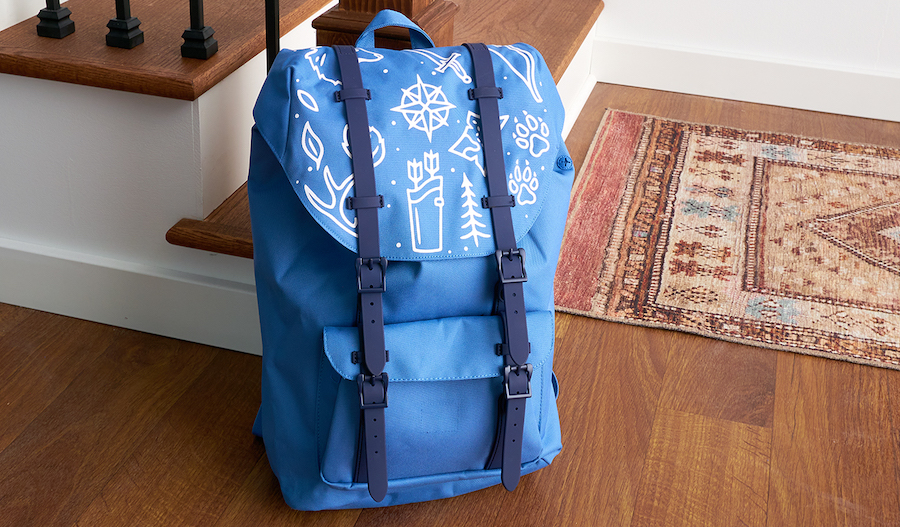 A blue adventure backpack with white iron-on camping decals sits on wood flooring