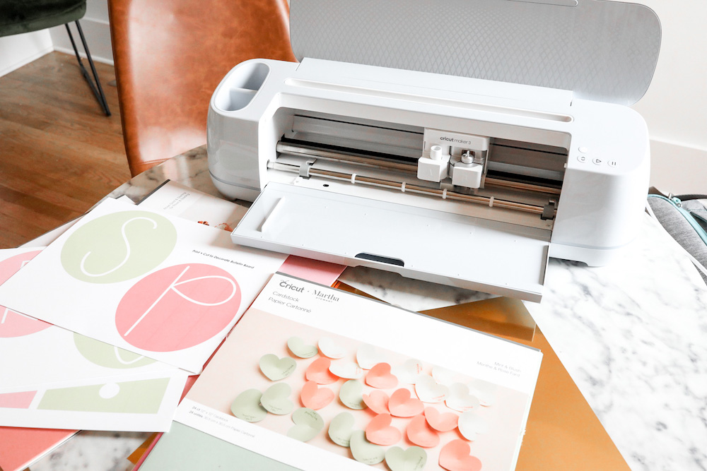 A Cricut Maker 3 machine and cardstock used to make a bulletin board for back-to-school