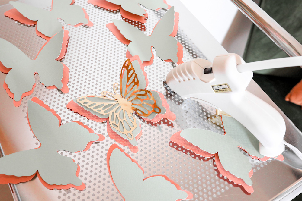 Cardstock butterflies are adhered together in layered to act as decoration for a back-to-school bulletin board