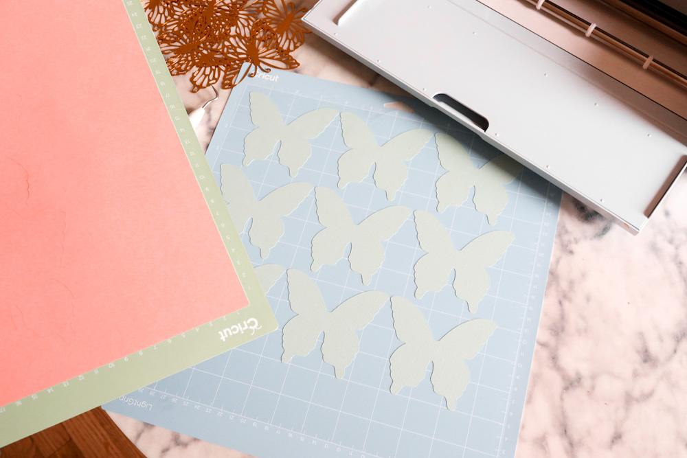 Green butterflies cut for use on a back-to-school bulletin board sit on a blue Cricut Grip mat