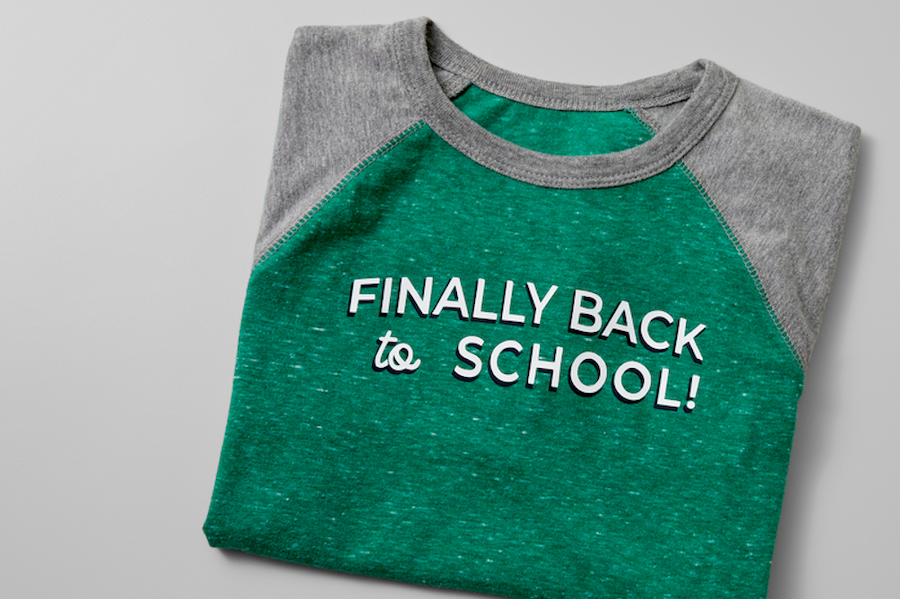 """A green back-to-school t-shirt with an iron-on decal reading """"finally back to school"""" sits on a grey background"""
