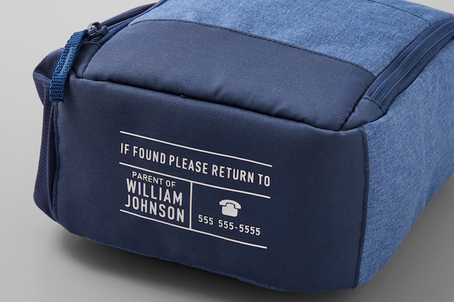 A blue backpack has a white lost and found label ironed-on to the bottom, making sure that all back-to-school supplies can be returned to their owner if lost