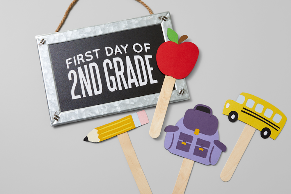 Photoshoot props showing a pencil, backpack, apple, bus, and other back-to-school supplies sit on a grey background