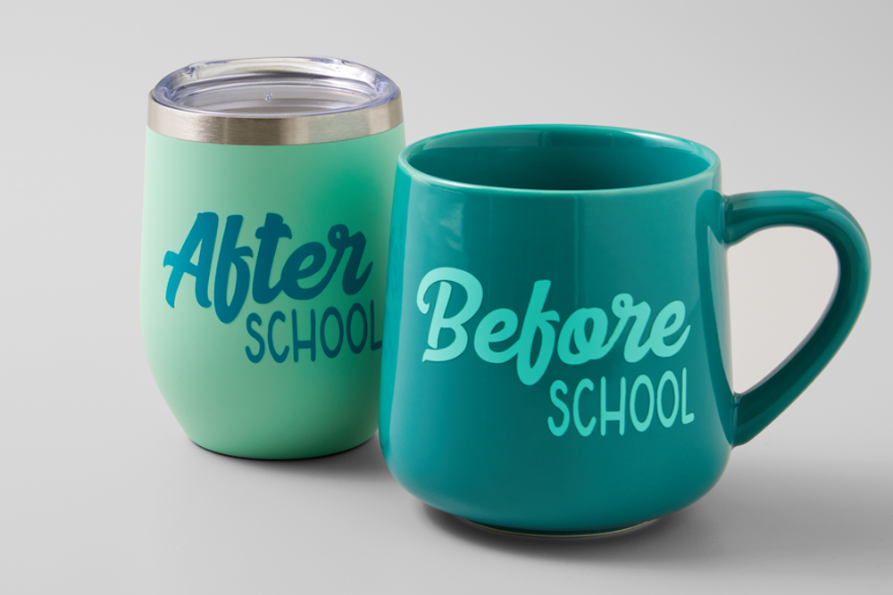 A green and teal mug and tumbler set sit on a grey background