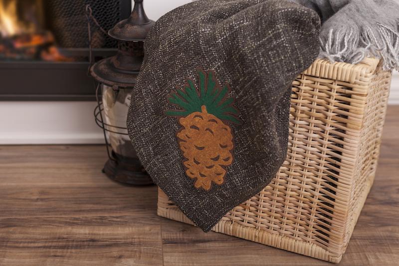 A custom cabin blanket sits in a wicker basket