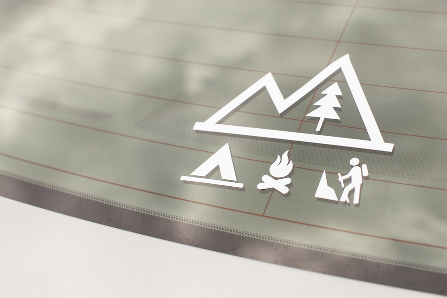 A white vinyl decal depicts a camping scene on the back windshield of a car