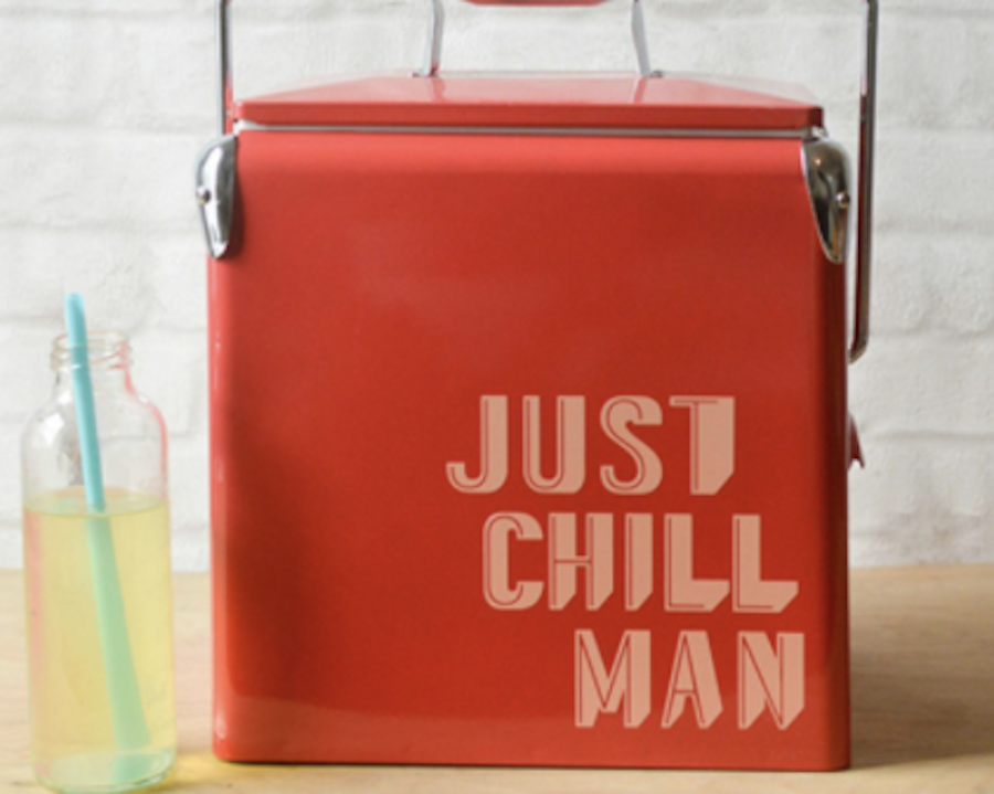 A red camping cooler sits on a wooden countertop next to a glass of lemonade