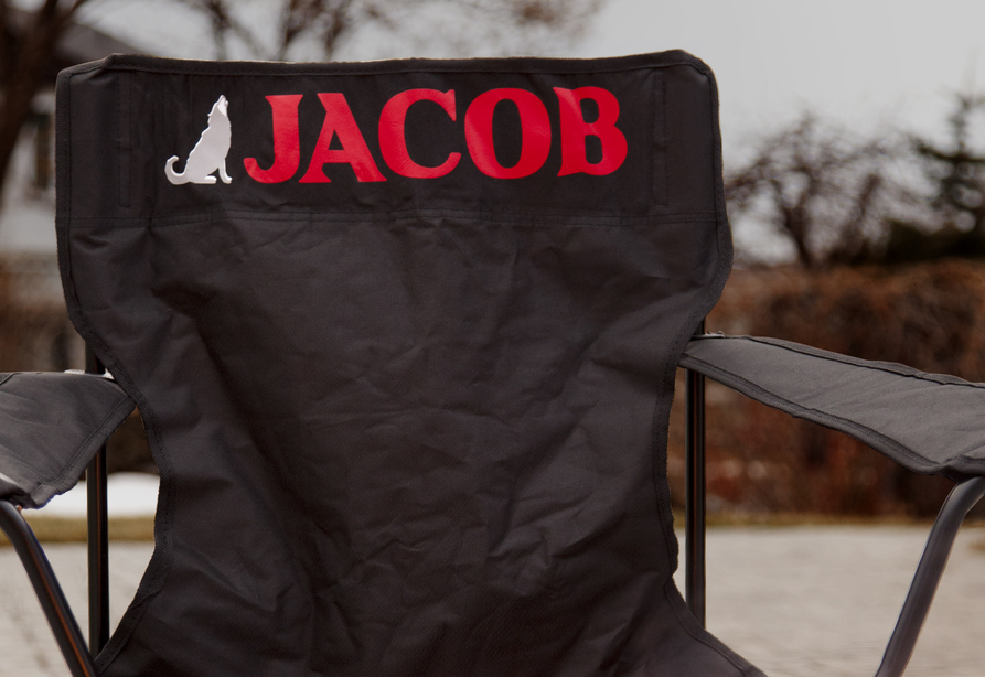 """A personalized black folding chair has a wolf decal next to the name """"Jacob"""" which is adhered in bright red vinyl"""