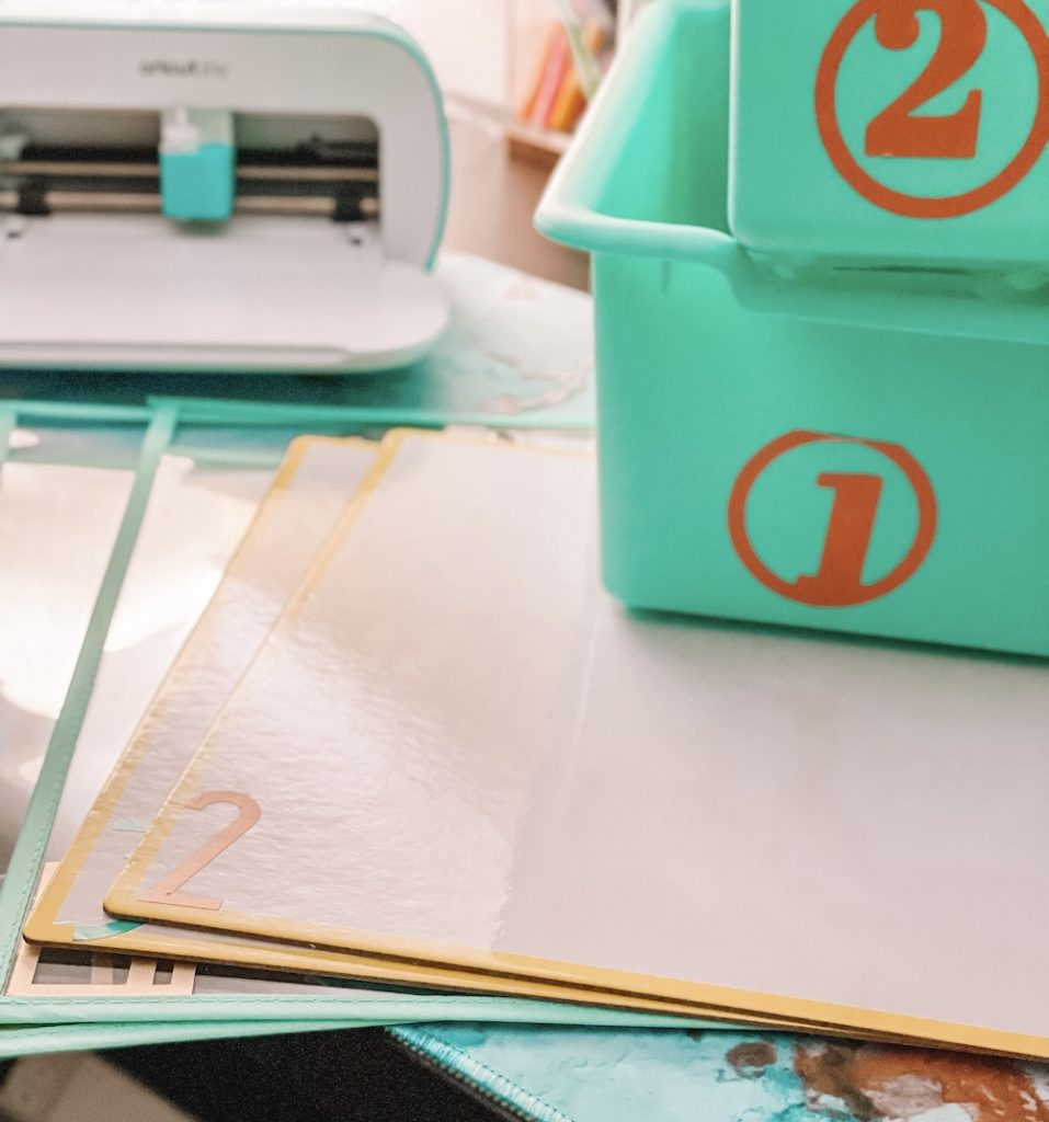 Tote bins and whiteboards are customized with orange vinyl labels as a back-to-school classroom organization project