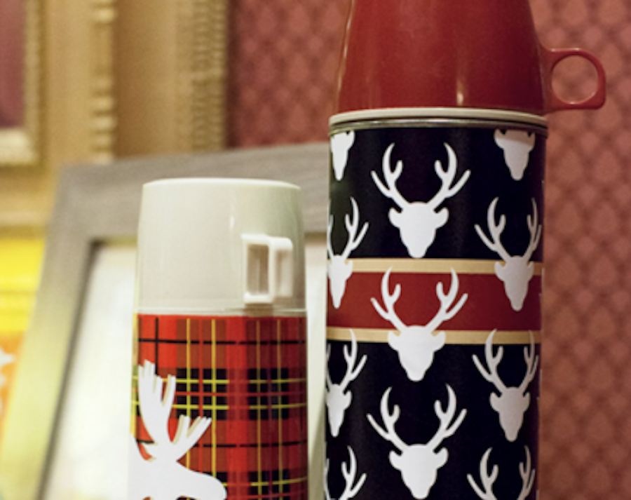 Retro and vintage looking thermos with deer and moose designs sit on a countertop