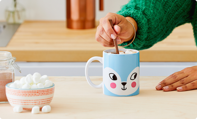 Hand stirring hot cocoa with marshmallows in a Cricut-customized mug on a kitchen counter
