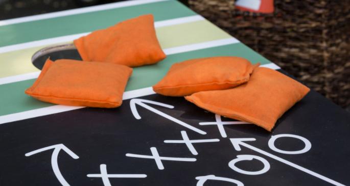Cornhole board and orange beanbags with football play design