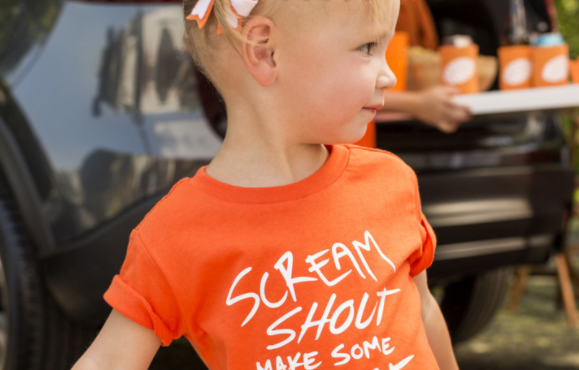 """orange shirt on young child that reads """"Scream, Shout, Make Some Noise"""""""