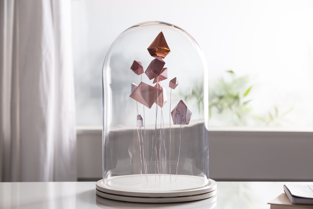 A gem cloche holding handmade cardstock crystals sits on a tabletop