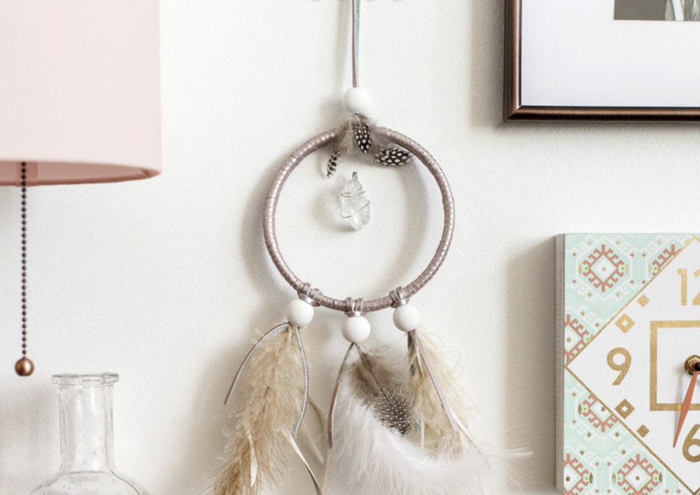 A dreamcatcher bound in pink faux leather and feathers holds a suspended silver crystal in the center of its shape