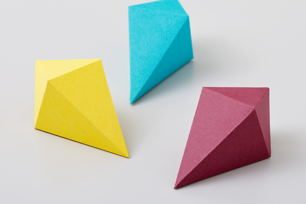 3D cardstock gems in blue, yellow, and red sit on a white countertop