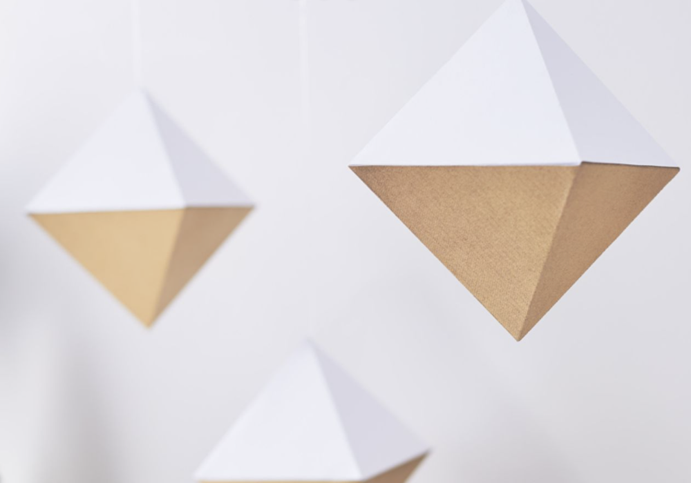 Hanging cardstock ornaments in the shape of crystals are suspended on a white background