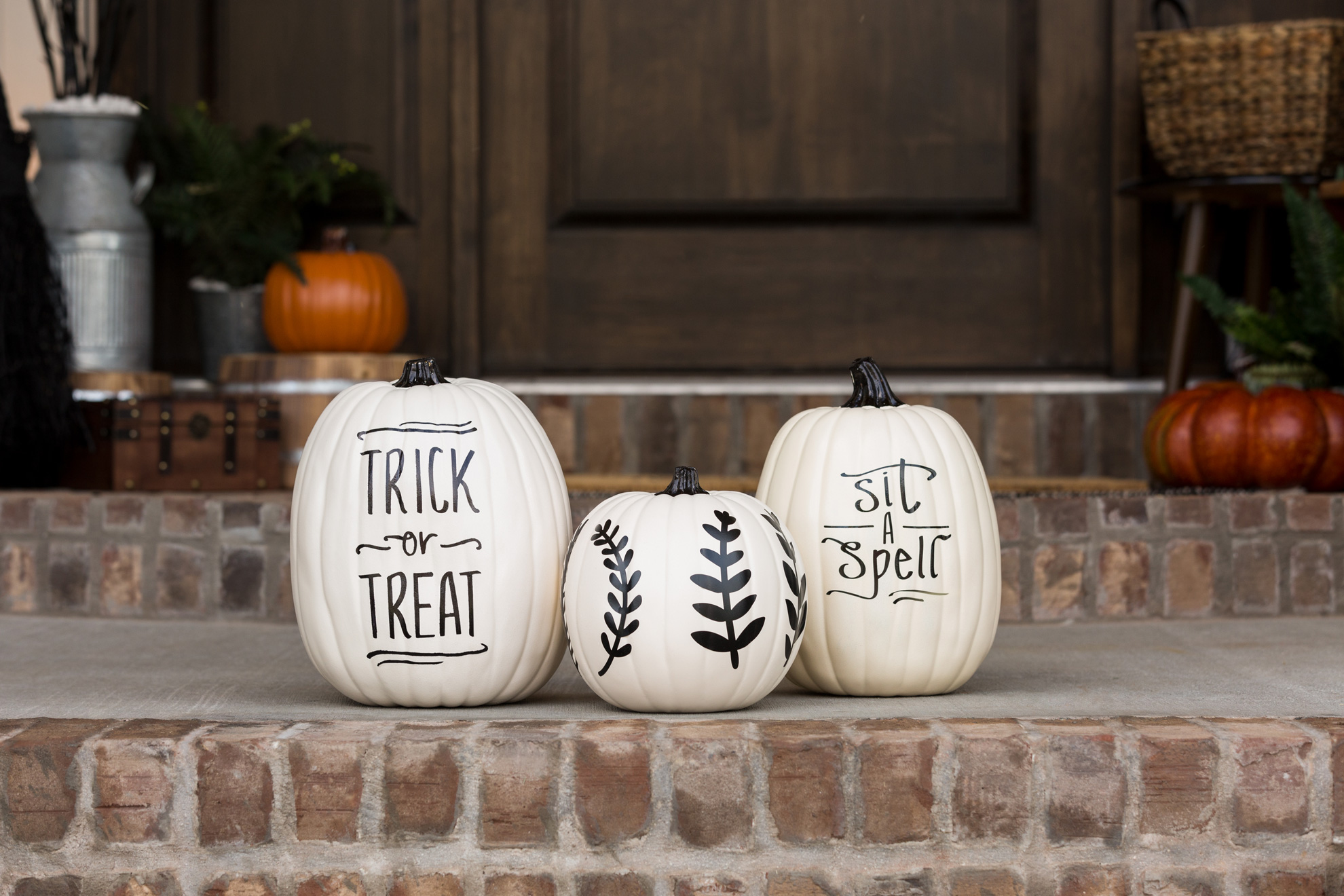 Decorated pumpkins sitting on an outdoor step