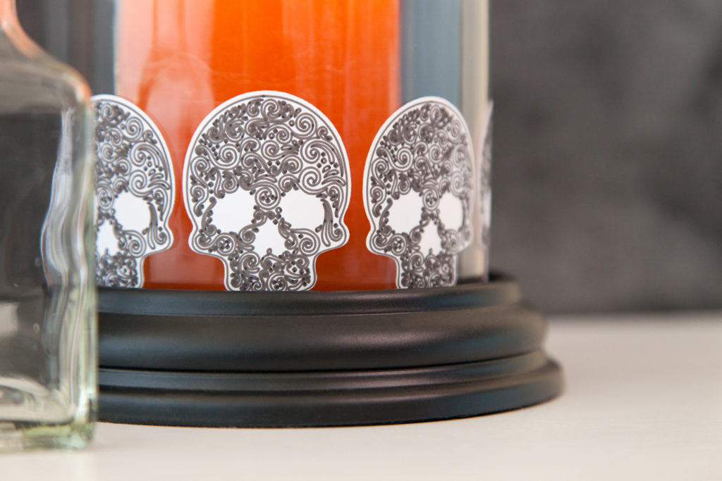 Orange Halloween candle in jar decorated with skull stickers