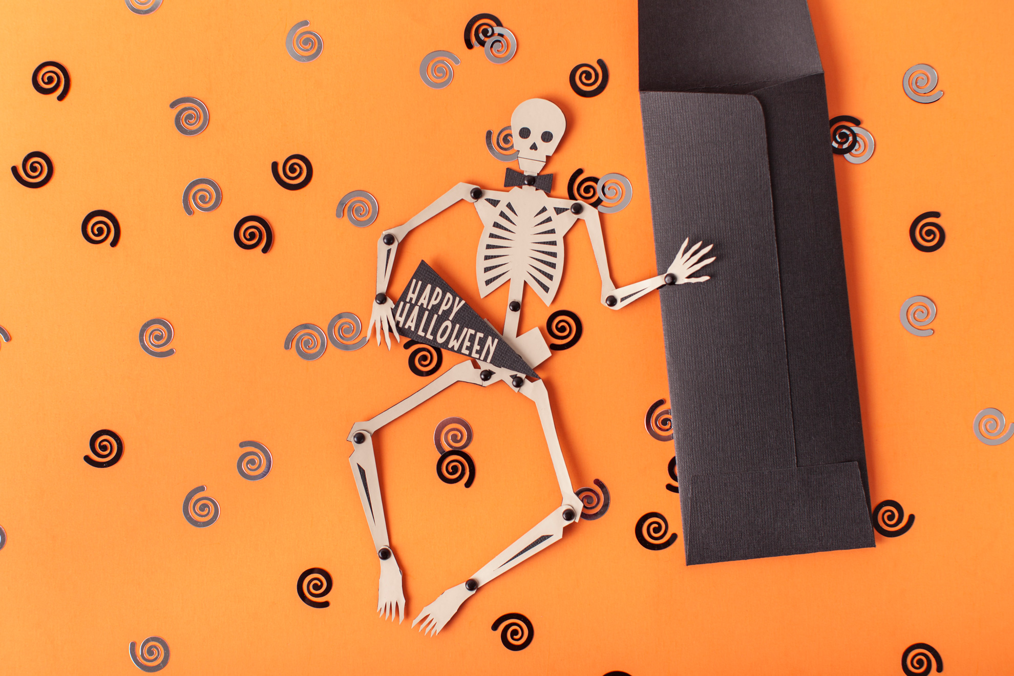 Paper skeleton and decorations on an orange background