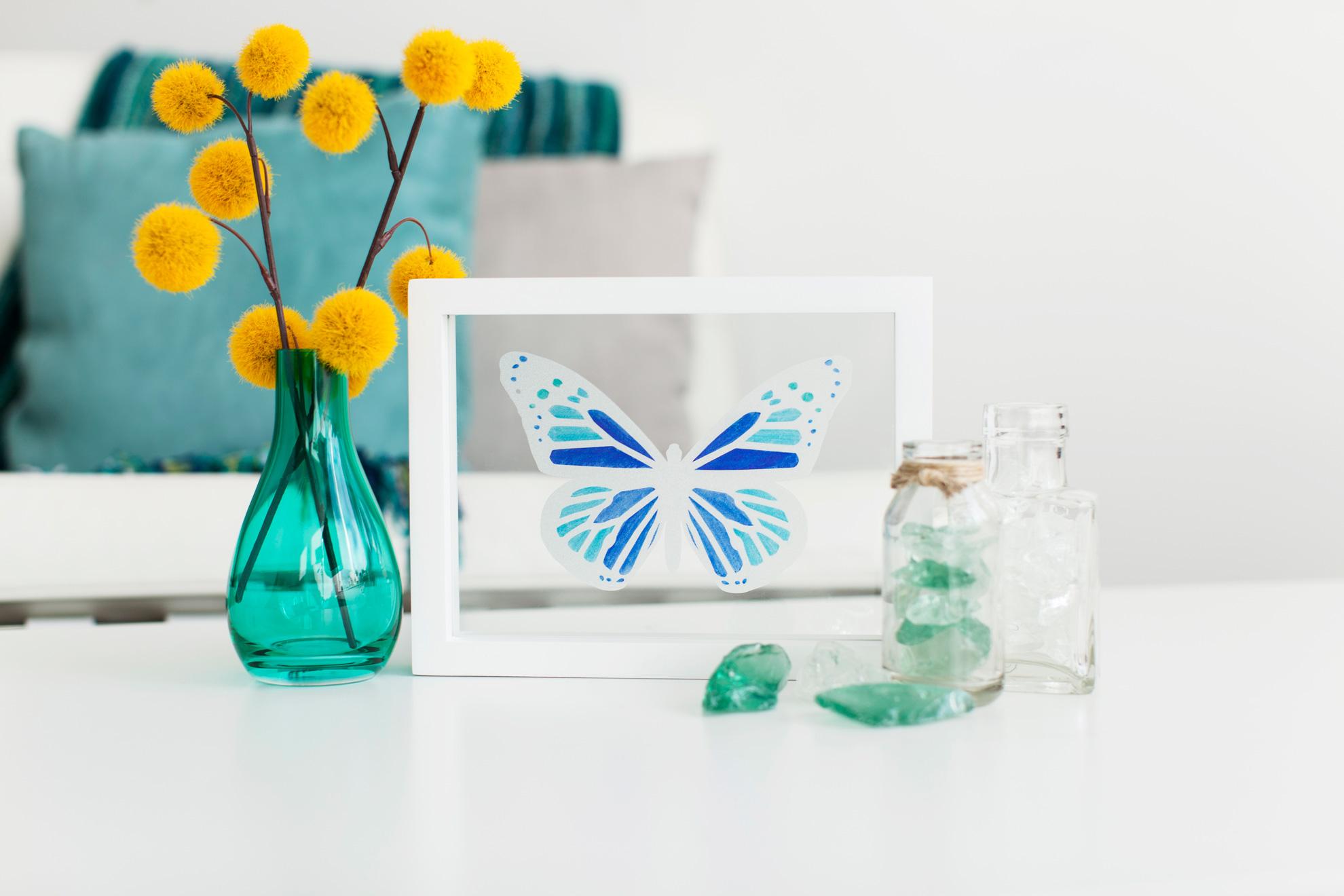 butterfly design inside white frame on table